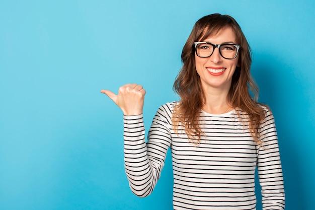 Das porträt einer jungen freundlichen frau mit einem lächeln in einem lässigen t-shirt und einer brille zeigt einen finger zur seite auf licht. emotionales gesicht. geste schau es dir an, pass auf