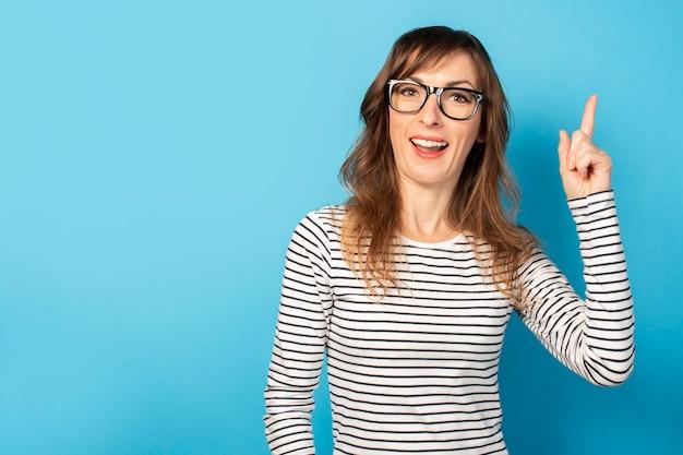 Das porträt einer jungen freundlichen frau mit einem überraschten gesicht in einem lässigen t-shirt und einer brille zeigt einen finger auf blau nach oben. emotionales gesicht. gestenidee, eureka