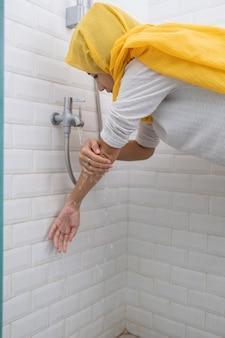 Das porträt einer jungen muslimischen frau führt vor dem gebet zu hause eine waschung (wudhu) durch