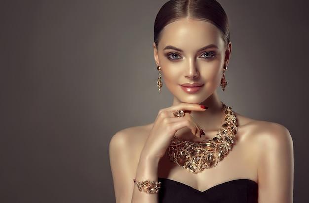 Das porträt einer jungen, wunderschönen frau trägt ein schmuckset aus einem halskettenring und ohrringen. hübsches blauäugiges modell mit einem sanften lächeln im gesicht in elegantem abend-make-up. schönheit und stil
