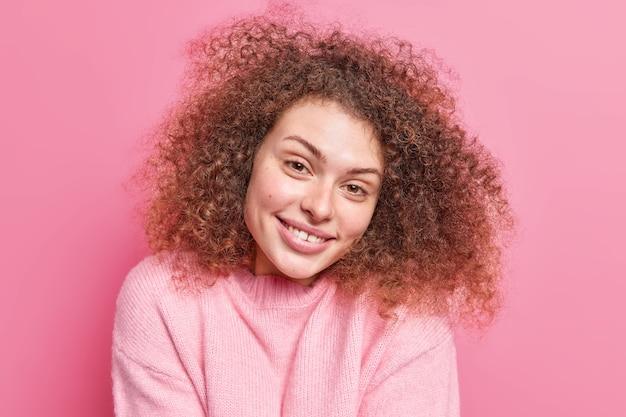 Das porträt einer positiven verführerischen frau mit lockigem, buschigem haar lächelt sanft und zeigt, dass weiße zähne gesunde haut haben und einen lässigen pullover einzeln über einer rosafarbenen wand tragen. natürliches schönheitskonzept