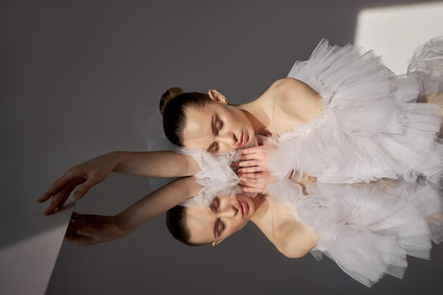 Das porträt einer romantischen schönheitsfrau in einem hellen kleid spiegelt sich im spiegel wider. naturkosmetik, schöne glatte gesichtshaut, haarknoten