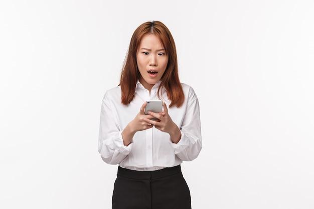 Das porträt einer schockierten und sprachlosen asiatischen frau, die erschrocken auf das smartphone-display starrte, mit gesenktem kiefer erschrocken nach luft schnappte und besorgt auf den handybildschirm schaute, fand heraus, dass ihr freund sie betrog