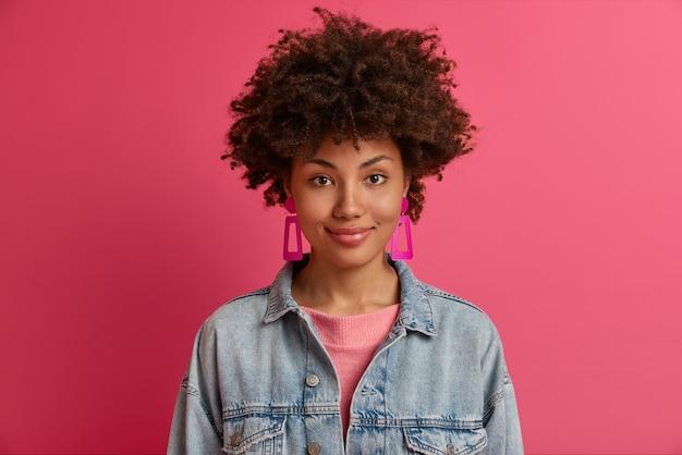 Das porträt einer schönen afroamerikanischen frau hat einen charmanten ausdruck, eine dunkle haut, trägt ohrringe und eine jeansjacke, sieht zufrieden aus und ist bereit, mit freunden auszugehen