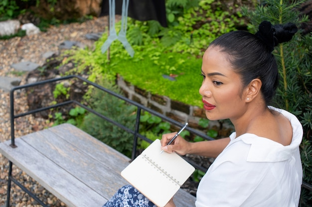 Das porträt einer schönen frau, die in ein buch schreibt, sitzt und denkt über den job im park nach, entspannen sie sich im freien zeitkonzept.