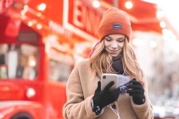 Das porträt einer schönen frau im kopfhörer steht auf dem hintergrund eines schönen stadtbokehs, benutzt ein smartphone und lächelt