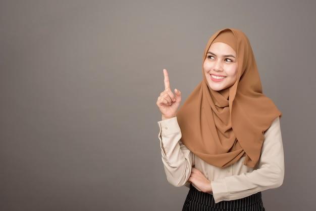 Das porträt einer schönen frau mit hijab zeigt etwas auf ihrer hand