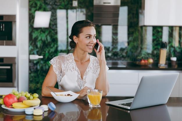 Das porträt einer schönen glücklichen frau, die beim frühstück mit laptop auf dem tisch telefoniert