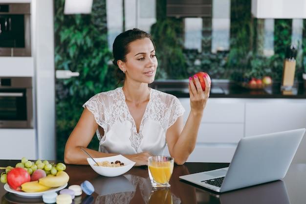 Das porträt einer schönen glücklichen frau, die beim frühstück mit müsli und milch mit laptop arbeitet