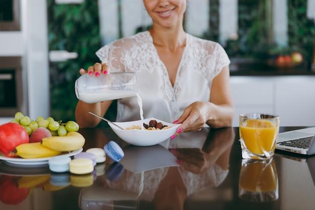 Das porträt einer schönen glücklichen frau, die milch in eine schüssel mit müsli zum frühstück mit einem laptop auf dem tisch gießt