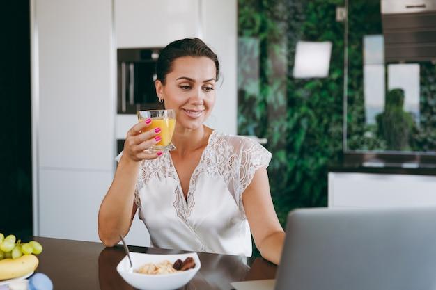 Das porträt einer schönen jungen frau, die beim frühstück mit müsli und milch mit laptop arbeitet und orangensaft trinkt