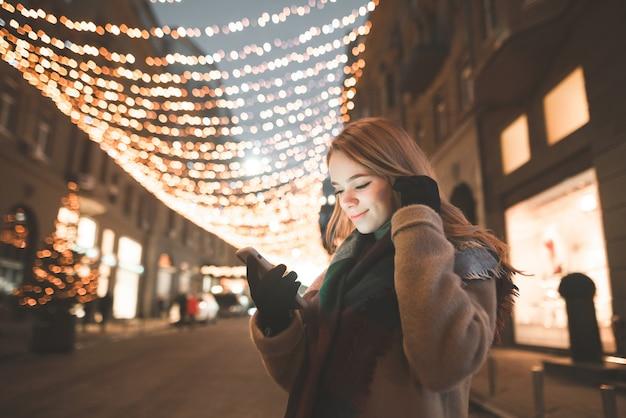 Das porträt einer süßen dame in warmen kleidern benutzt ein smartphone, schaut auf den bildschirm und lächelt bei einem abendspaziergang