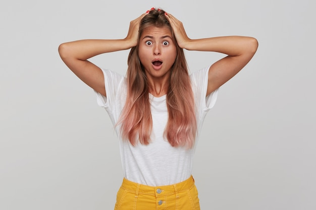 Das porträt einer verblüfften betäubten jungen frau mit langen, pastellrosa haaren und geöffnetem mund hält die hände auf dem kopf und schreit isoliert über der weißen wand