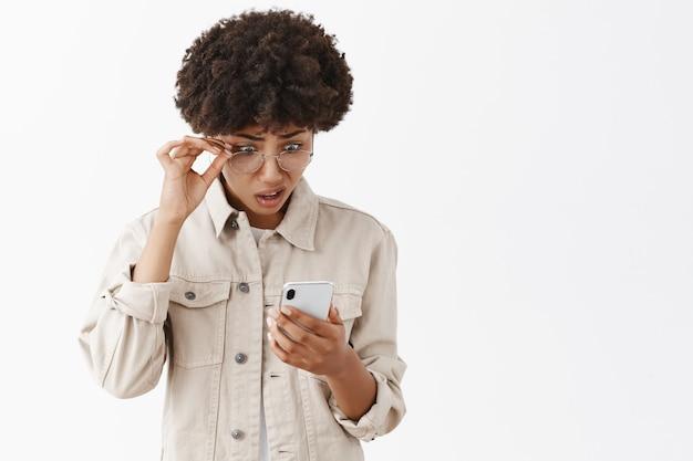 Das porträt einer verwirrten und befragten intensiven afroamerikanerin kann nicht an unsinn glauben, den sie über smarpthone las, die brille abnahm, das gesicht verzog und mit stupor auf den bildschirm schaute