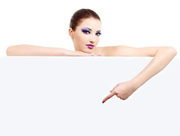 Das porträt einer weiblichen mode-person zeigt auf das leere banner auf weiß