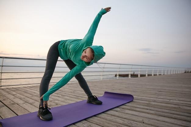 Das porträt einer wunderschönen jungen frau, die yoga praktiziert, sportkleidung trägt, lässt den morgen am meer dehnen. gesundheitskonzept.