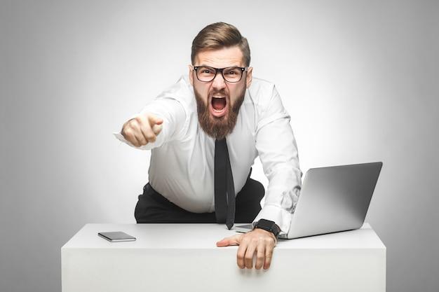 Das porträt eines aggressiven, unglücklichen jungen geschäftsmannes in weißem hemd und schwarzer krawatte beschuldigt sie im büro und hat schlechte laune, schreit und zeigt mit dem finger auf die kamera und schreit. innenaufnahme, studioaufnahme