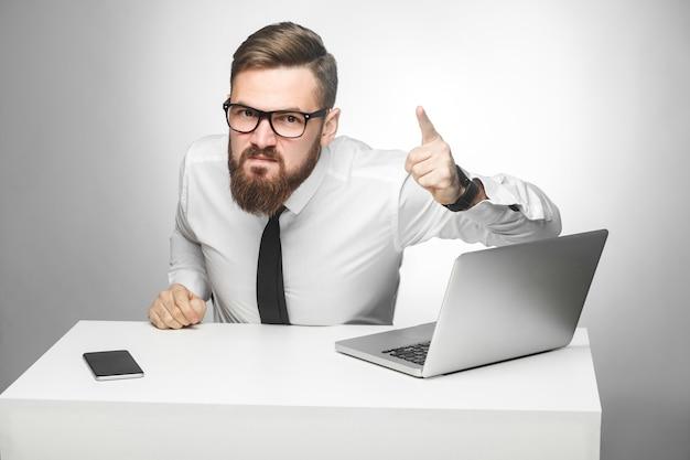 Das porträt eines aggressiven, unglücklichen jungen geschäftsmannes in weißem hemd und schwarzer krawatte beschuldigt sie im büro und hat schlechte laune, schreit und zeigt mit geöffnetem mund mit dem finger auf sie. innenaufnahme, studioaufnahme