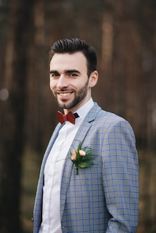 Das porträt eines attraktiven bräutigams in anzug und fliege mit boutonniere oder knopfloch auf jacke steht vor dem hintergrund des waldes in der natur.