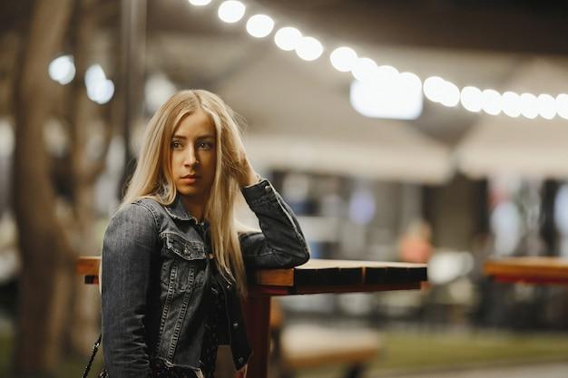 Das porträt eines attraktiven jungen blonden kaukasischen mädchens nahe dem hohen couchtisch im freien schaut ernsthaft zur seite, gekleidet in jeansjacke unter abendgirlandenbeleuchtung