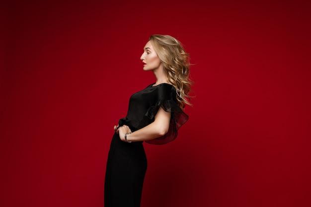 Das porträt eines attraktiven weiblichen modemodells mit braunen haaren steht neben der kamera