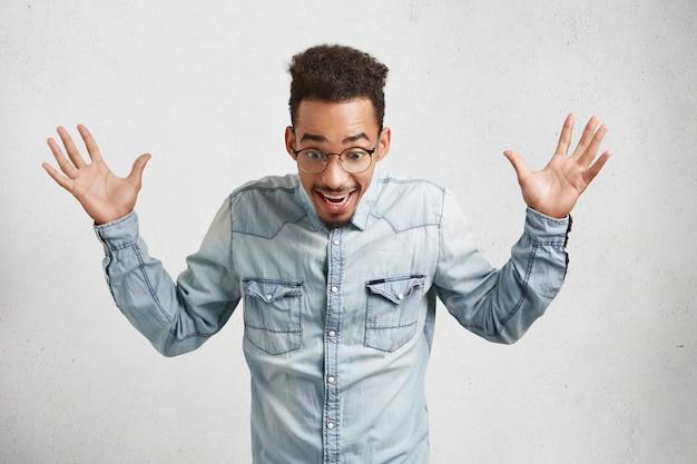 Das porträt eines aufgeregten bärtigen afroamerikaners trägt ein lässiges jeanshemd und eine runde brille