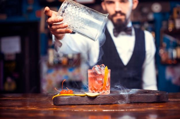 Das porträt eines barmanns gießt an der bar einen drink ein