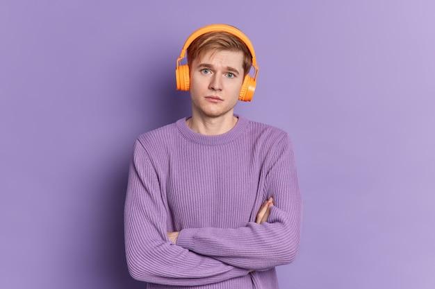Das porträt eines ernsthaften gutaussehenden teenagerjungen steht mit verschränkten armen und schaut in die kamera, trägt kopfhörer und pulloverposen