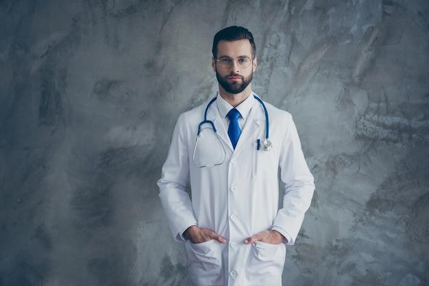 Das porträt eines ernsthaften talentierten arztes steckte seine hände in taschen mit weißem kittel, um patienten in einer klinik zu heilen, die über einer grauen farbwand isoliert war