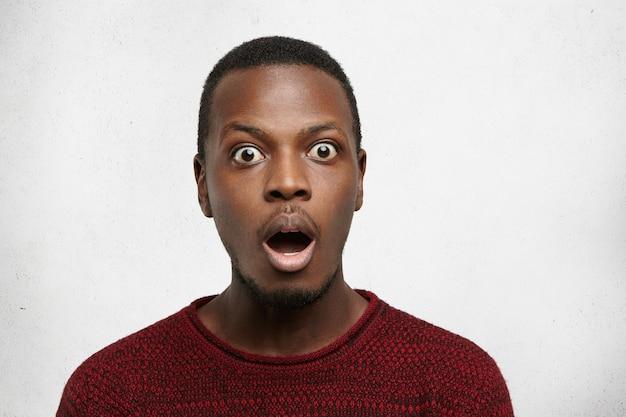 Das porträt eines erstaunten jungen afroamerikaners mit käferaugen, der lässig gekleidet mit dem mund gekleidet war, fiel auf und der kiefer fiel herunter