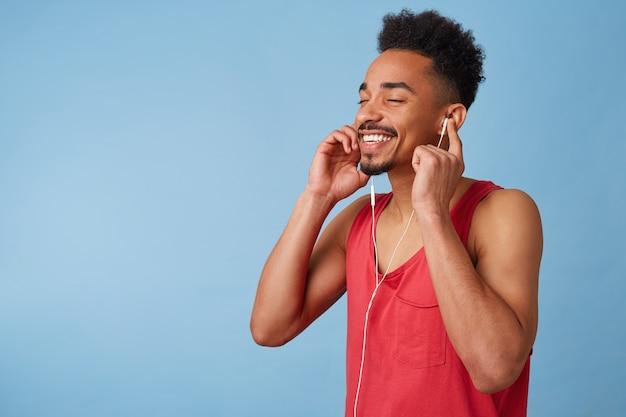 Das porträt eines freudigen jungen afroamerikaners fühlt sich großartig an, trägt kopfhörer, schließt die augen und genießt ein neues album der lieblingsband, isoliert.