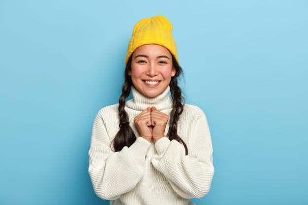 Das porträt eines fröhlichen jungen mädchens hält die hände zusammen, lächelt angenehm in die kamera, genießt positive nachrichten, trägt einen gelben hut und einen weißen übergroßen pullover