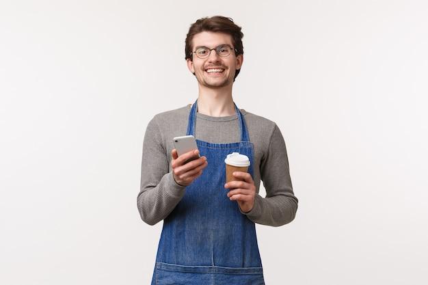Das porträt eines fröhlichen jungen männlichen angestellten schlägt vor, den gutscheincode mit der handy-app zu verwenden, um rabatt in seinem café zu erhalten, das eine tasse zum mitnehmen und eine lächelnde smartphone-kamera hält
