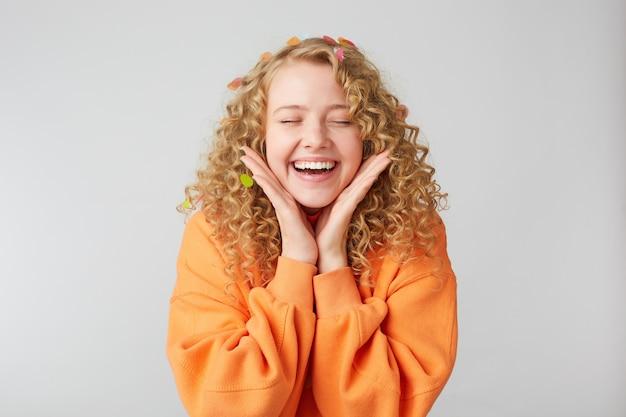 Das porträt eines fröhlichen schönen mädchens, das einen orangefarbenen pullover trägt, hält die handflächen in der nähe des gesichts und feiert mit geschlossenen augen, die vor vergnügen über der weißen wand isoliert sind