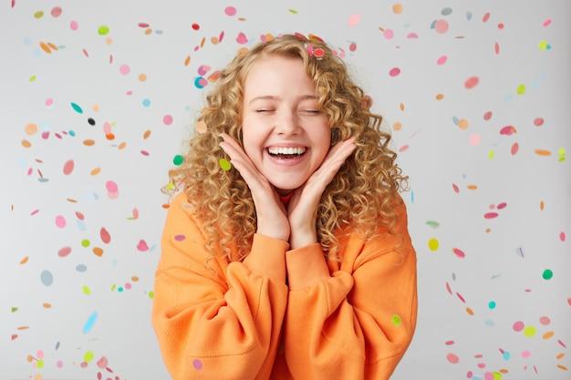 Das porträt eines fröhlichen schönen mädchens, das einen orangefarbenen pullover trägt, hält die handflächen nahe dem gesicht stehend und feiert mit geschlossenen augen vor vergnügen unter konfetti-regen und feiert isoliert über der weißen wand