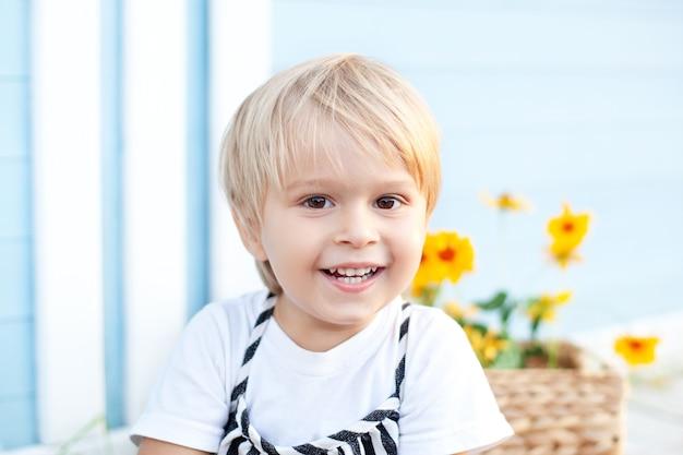 Das porträt eines glücklichen blonden jungenkindes lächelt, genießt das leben. porträt eines jungen in der natur, im park, im freien. das konzept einer glücklichen familie und elternschaft. kindheitskonzept. charmantes baby. sommer-