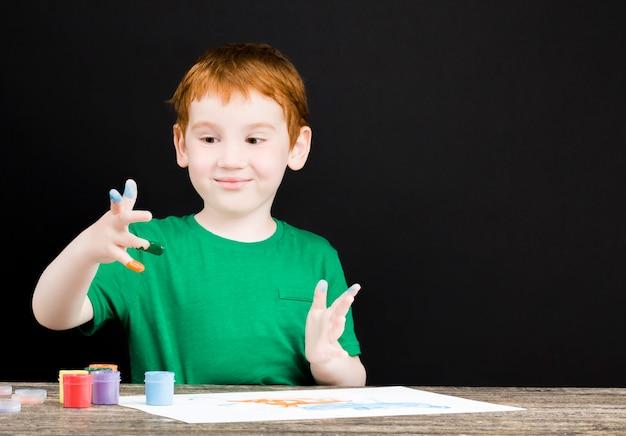 Das porträt eines glücklichen kleinen rothaarigen jungen zeichnet auf papier mit farben verschiedener farben, der junge zeichnet mit seinen händen und so werden seine hände in blau, rot und anderen farben gemalt