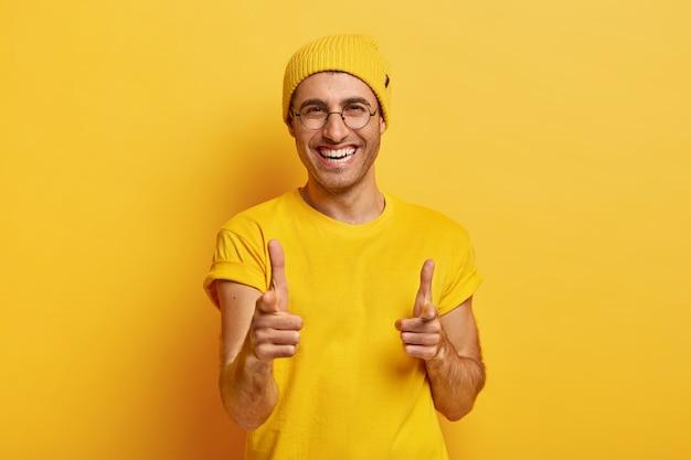 Das porträt eines glücklichen mannes zeigt mit den vorderfingern auf die kamera, wählt sie aus, schaut fröhlich in die kamera und lächelt breit