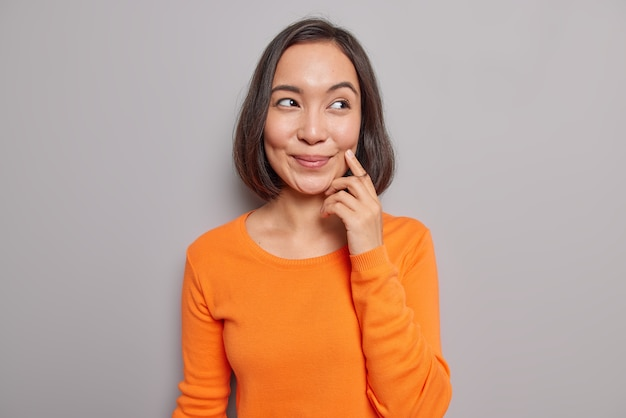 Das porträt eines gut aussehenden asiatischen weiblichen models erinnert sich an ihr erstes date mit ihrem ehemann hat einen verträumten, fröhlichen ausdruck, lächelt sanft konzentriert und trägt einen lässigen orangefarbenen pullover, der drinnen gegen eine graue wand posiert