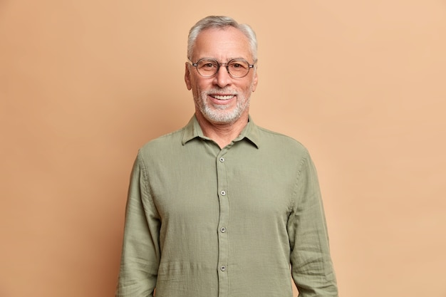 Das porträt eines gutaussehenden älteren europäischen mannes lächelt positiv genießt ruhestand trägt hemd und brille hat perfekte weiße zähne, die über beige studiowand isoliert werden
