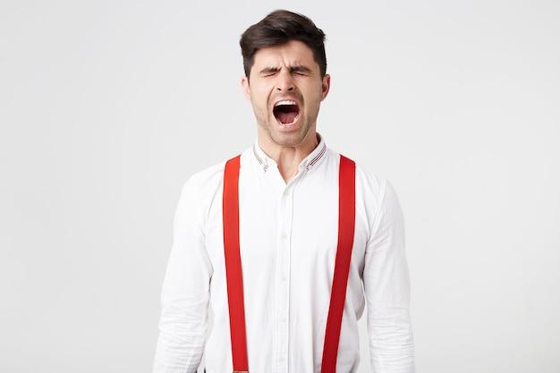 Das porträt eines gutaussehenden mannes wacht auf, gähnt mit geschlossenen augen, trägt hemd und rote hosenträger und hat nicht müde geschlafen