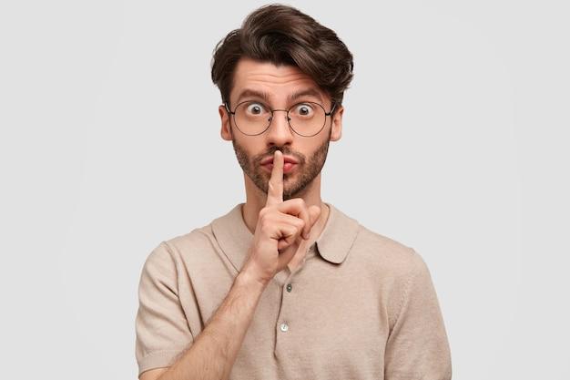 Das porträt eines gutaussehenden unrasierten mannes hält den vorderfinger auf den lippen