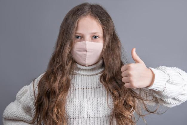 Das porträt eines jungen attraktiven kleinen mädchens mit einem weißen pullover in einer medizinischen schutzmaske zeigt daumen hoch, wie platz für text. speicherplatz kopieren
