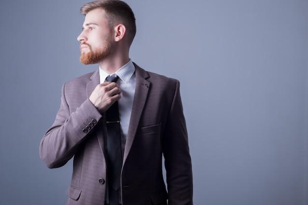 Das porträt eines jungen bärtigen, gutaussehenden mannes von fünfundzwanzig jahren in einem offiziellen anzug zieht seine krawatte fest.
