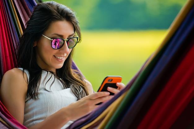 Das porträt eines jungen brünetten mädchens mit sonnenbrille liegt in einer hängematte und spielt mit dem handy. nahansicht.