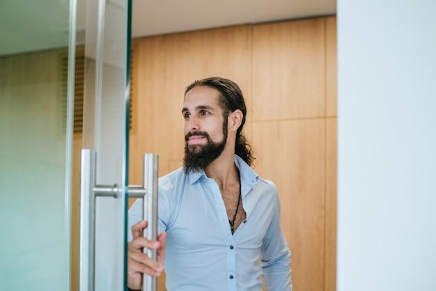Das porträt eines jungen geschäftsmannes öffnet die tür zum büro