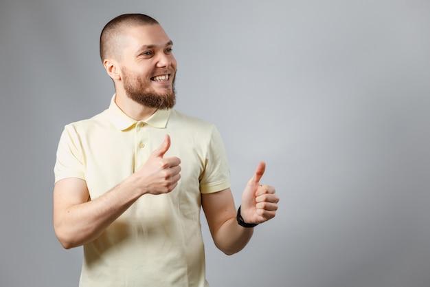 Das porträt eines jungen mannes in einem gelben t-shirt zeigt sich wie auf grau.