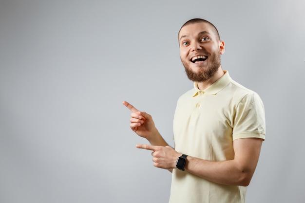 Das porträt eines jungen mannes in einem gelben t-shirt zeigt zur seite auf grau.
