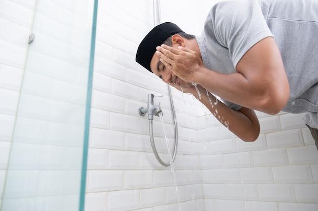 Das porträt eines jungen muslimischen mannes führt vor dem gebet zu hause eine waschung (wudhu) durch