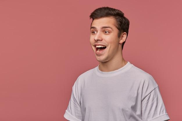 Das porträt eines jungen überraschten mannes trägt ein leeres t-shirt, hört unglaubliche neuigkeiten, steht auf rosa mit kopierraum, weit geöffnetem mund in schockiertem ausdruck.